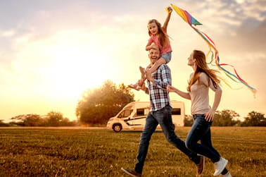 Family running across a field holding a kite