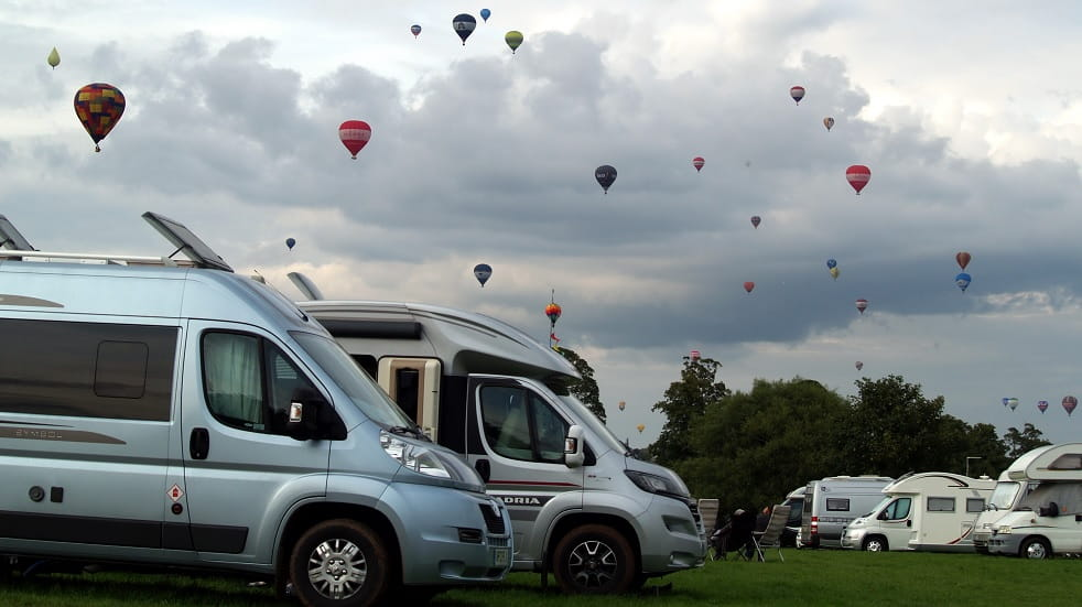 Campervans with hot air balloons in the sky behind them from Bristol Balloon Fiesta