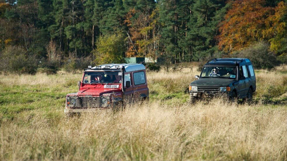 Two 4x4 vehicles driving through the countryside