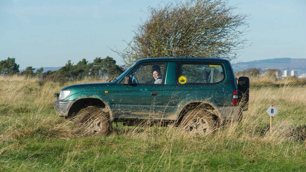 Side view of a 4x4 going through through the countryside