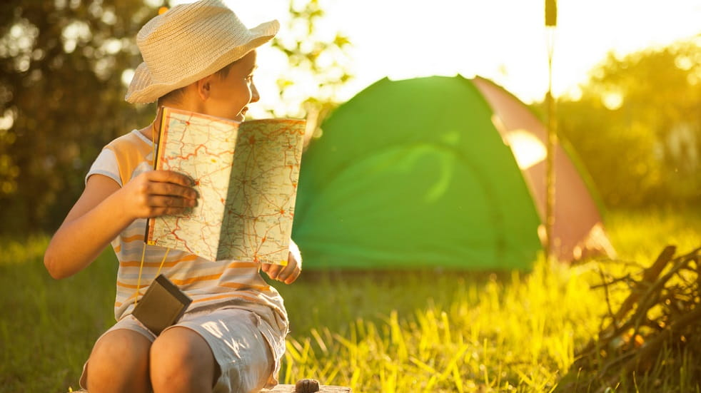 Boy camping holding a map