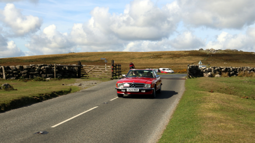 Red Triumph TR6 driving through the country with a stone wall behind it
