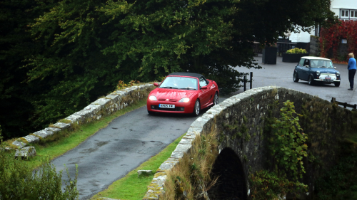 A red classic convertible going over a brick bridge in a village