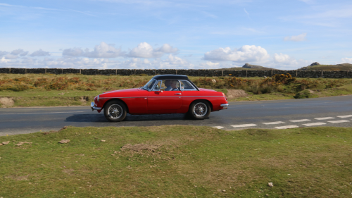 Side view of red Jensen-Healey in the countryside