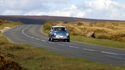 Front view of a classic Mini driving through the countryside
