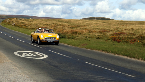 Front view of yellow Triumph TR6 driving through the countryside