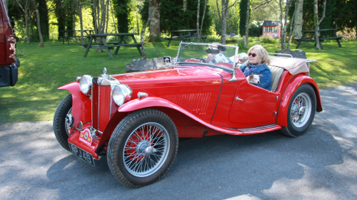 A red classic car with a woodland picnic area behind it