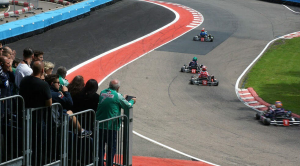 Karts being photographed racing around a track
