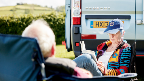 Two people relaxing outside their campervan