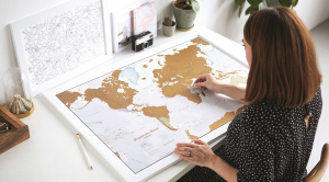 Framed map print with woman scratching off countries