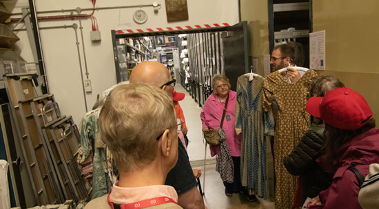 Group of people looking at old dresses