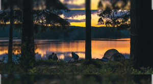 People camping by a lake at sunset