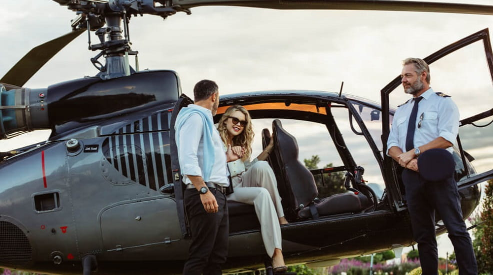 Woman boarding a helicopter with the pilot standing beside it