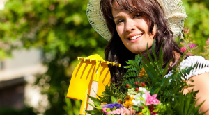 A woman in a sunhat in the garden with a few yellow tools and flowers