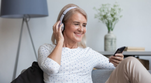 Woman wearing headphones learning a new language through her phone
