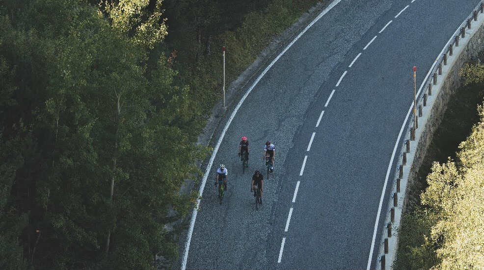 4 cyclists riding on a road together
