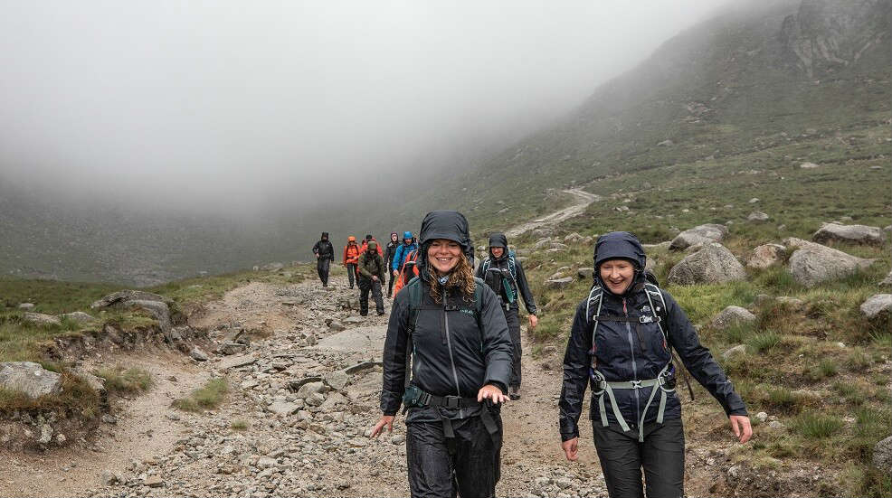 People walking up a mountain with waterproofs on