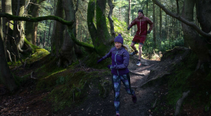 Two people running through the forest