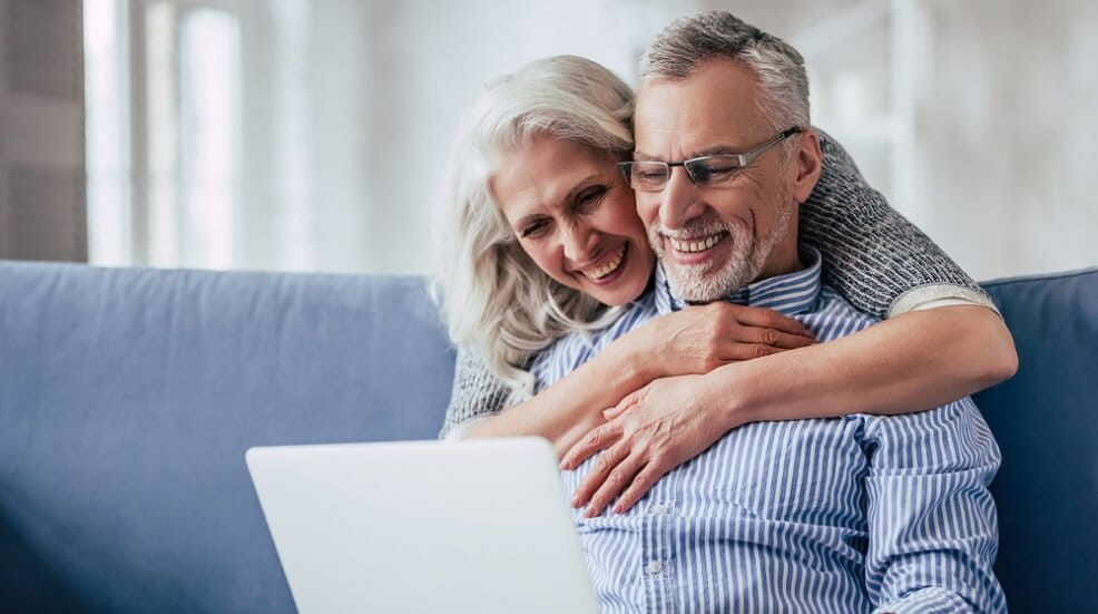 Couple looking at a laptop together and smiling