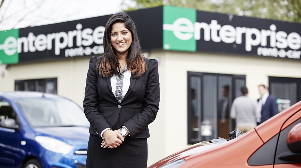 Woman in smart clothes standing in front of an enterprise rent-a-car building