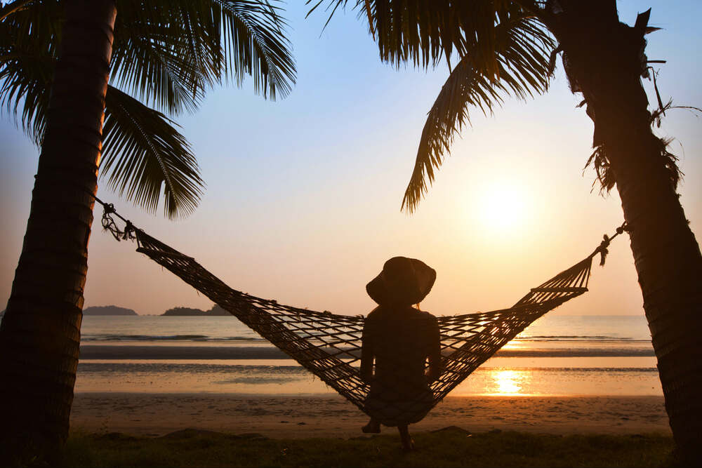 silhouette of woman in hat sitting alone in hammock at sunset on the beach