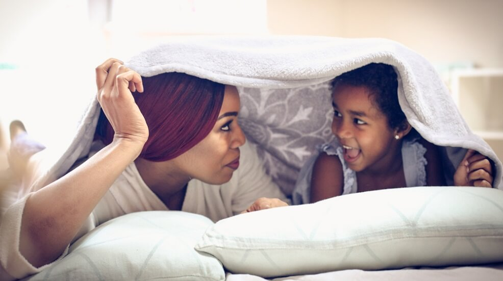 Mum and daughter talking under a cover