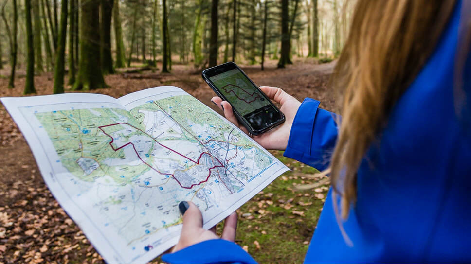 Women tracking her route on map and phone