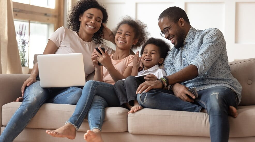 A family on the sofa looking at a laptop