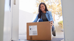 Woman picking up a box that has been delivered to her door