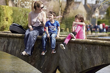 Family sitting on a footbridge Cotswolds