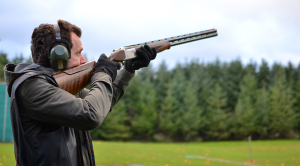 Person taking aim at airborne clay pigeon