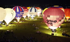 Hot air balloons on the ground lit up at night