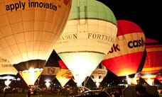 Flames lit under hot air balloons at night