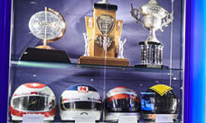F1 trophy cabinet with drivers helmets on display