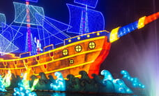 Ship lit up at night with mermaids surrounding