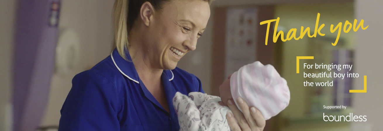 Smiling midwife holding a baby