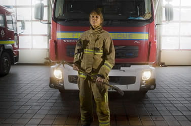 Fire service woman standing in front of a fire truck