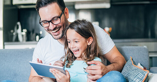 father and daughter looking at a tablet